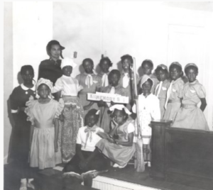 Photograph showing Norma T. Roberts posing with a group of Black girls. The girls are dressed in pioneer style or Sunbeam dresses.