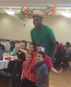 Photograph showing Captain AJ Zimmerman wearing a green polo shirt and an inflatable moose antler ring toss game on his head. A group of children stand with him.
