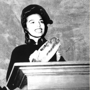 Graphic button showing a picture of Major Norma Roberts wearing a Salvation Army bonnet and playing a tambourine as she stands behind a wood podium