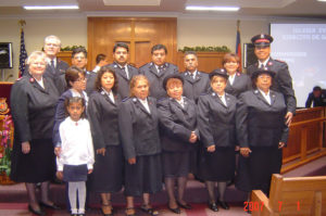 Photo showing a group of men and women standing in two rows. They all wear Salvation Army Soldier or officer uniforms. A girl stands in front of her mother. The group are standing inside a church, a wood cross can be seen in the background.