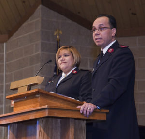 Photograph showing Captains Enrique and Nancy Azuaje wearing Salvation Army uniforms and standing behind a wood podium. They are in a room with cinder block walls.