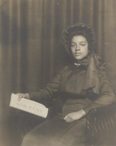 Photograph of Ensign Mable Broom. She is wearing a long Salvation Army dress and large bonnet which were part of the uniform in the early 1900s. She is seated in front of a drapery and holding a copy of The War Cry newspaper.
