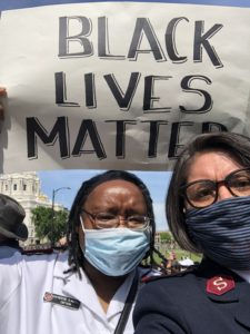 "Major Katherine Clausell and another female Salvation Army officer wear face masks during a peaceful demonstration in Washington D.C. in 2020. Clausell holds a sign above her head that reads ""Black Lives Matter."""