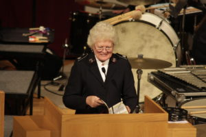 Photograph of Commissioner Eva Gaither preaching. She holds a bible and stands behind a large wood podium. Instruments from a band can be seen behind her. They include a bass drum and xylophone.