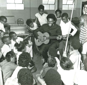 Photograph showing a Lt. Stephen Harper holding a guitar and smiling. He is surrounded by children.