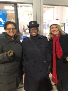A photograph showing three women wearing winter coats and hats. The woman on the far left, Major Cassandra DeJesus holds a handbell