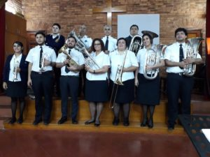 Photo of a Salvation Army brass band. The men and women wear white button down shirts and black pants or skirts. They stand in two rows with their instruments in the alter of the corps.