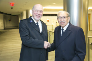 Photograph of two men shaking hands. They wear Salvation Army Soldier uniforms and are standing in an office building