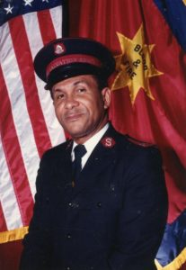 Photograph of Major Allan Wiltshire wearing a Salvation Army uniform. He is standing in front of Salvation Army and United States flags.