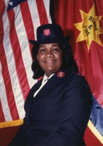 Photograph of Major Marjorie Wiltshire wearing a Salvation Army uniform. She stands in front of Salvation Army and United States flags