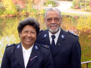 Color photograph of Envoys Roberto and Marina Santos wearing their Salvation Army uniforms. The smiling couple stands in front of a scenic outdoor pond.