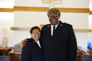 Photograph of Majors Stephen and Diane Harper. They are standing in front of a cross inside a church