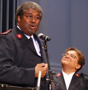 Photograph showing Majors Stephen and Diane Harper speaking at a microphone