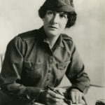 Black and white photograph of a woman wearing a WWI style uniform with cloth hat. She is seated at a desk and is writing on papers..