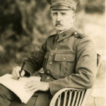 Black and white photograph of an older man with mustache wearing a WWI style military uniform. The man is seated in a chair with pieces of paper on his lap and a pen in his right hand. Trees can be seen in the background.