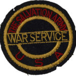 """Color photo of a fabric patch. The background fabric is black. Two circles are embroidered with gold tread. Inside the two circles is red text embroidered in red thread that reads """"The Salvation Army U S A."""" Over the circles is more text positioned horizontally, embroidered in gold tread, it reads """"War Service."""""""