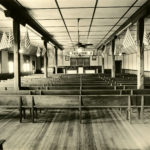 Black and white photograph of the interior of a large room. Wood timber support posts have US flags decorating them. Pews provide seating in the room.