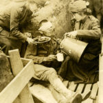 Black and white photograph of two Doughnut Girls serving coffee and doughnuts to a wounded man who sits either in a trench or outside a dugout.