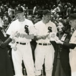 Black and white photo of three Chicago White Sox baseball club players purchasing Doughnut Day tags from two female Salvationists.