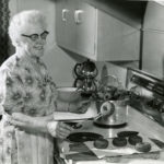 Black and white photo showing a woman with white hair and glasses, wearing a dress and fancy apron. She stands at the stove in her mid-20th century kitchen. She is frying doughnuts