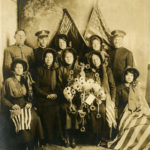 Black and white photo of a group of Salvationists wearing uniforms and bonnets. They pose with American flags and a wreath of flowers and doughnuts