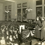 Black and white photo showing people in a chapel or lecture hall. Two Doughnut Girls and two male Salvation Army officers are on the stage.
