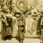 Black and white photograph showing two female Salvaiton Army officers wearing WWI uniforms collecting money in straw hats at a wood booth with a large doughnut hanging above the counter. A woman in fashionable dress makes a donation into the hat.
