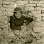 Black and white photograph showing a woman wearing a WWI M17 helmet and Salvation Army War Service uniform posing through a hole in a stone wall