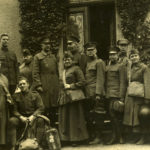 A black and white photograph showing a group of men and women all wearing military inspired Salvation Army WWI uniforms. The people have an assortment of luggage, M17 helmets, and gas masks in their bag holders