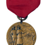 Photo of a pin on brass medal with red ribbon. The medal is circular and features a male and female Salvation Army War Service workers in front of a hut.