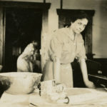 Black and white photo of a woman wearing a dress with the sleeves rolled up. She is making doughnuts at a table in a large WWI era kitchen.