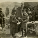 A black and white photograph showing US Army soldiers outside a tent. In the foreground a soldier on the left speaks with Lt. Colonel Edward Parker on the right. Parker carries a typewriter under his arm. Soldiers can be seen milling about in the background.